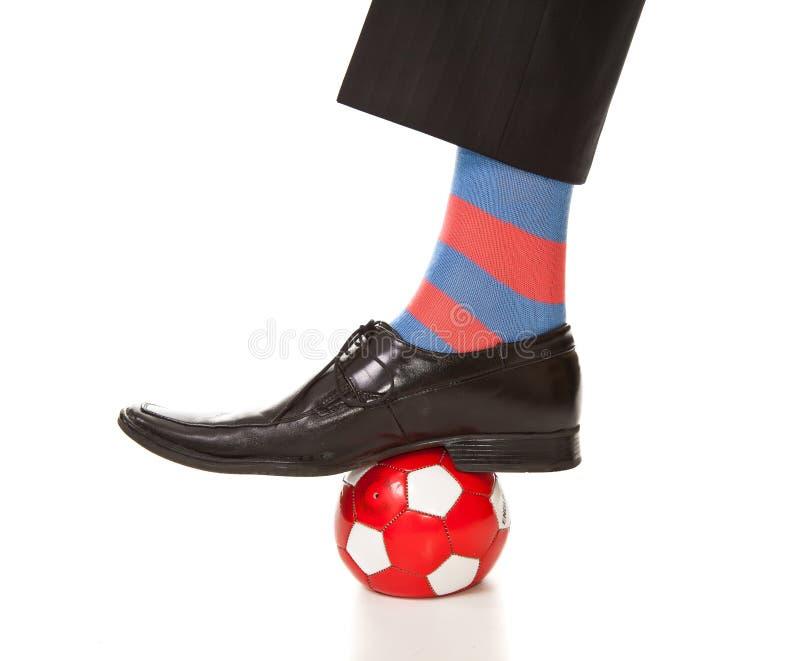 Pé do homem no terno com esfera de futebol imagens de stock