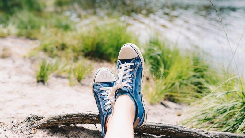 Pé e pés vistos de cima em uma praia arenosa do lago Selfie das sapatilhas na terra fotos de stock