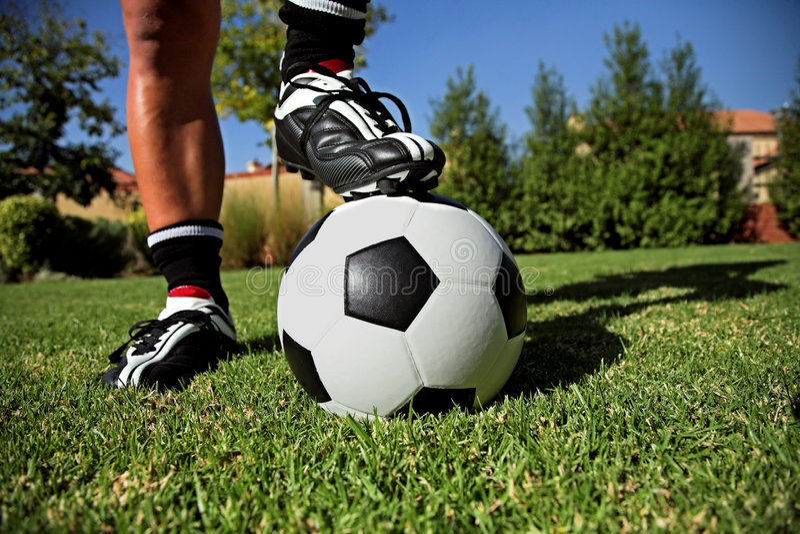 Pé em um soccerball fotografia de stock