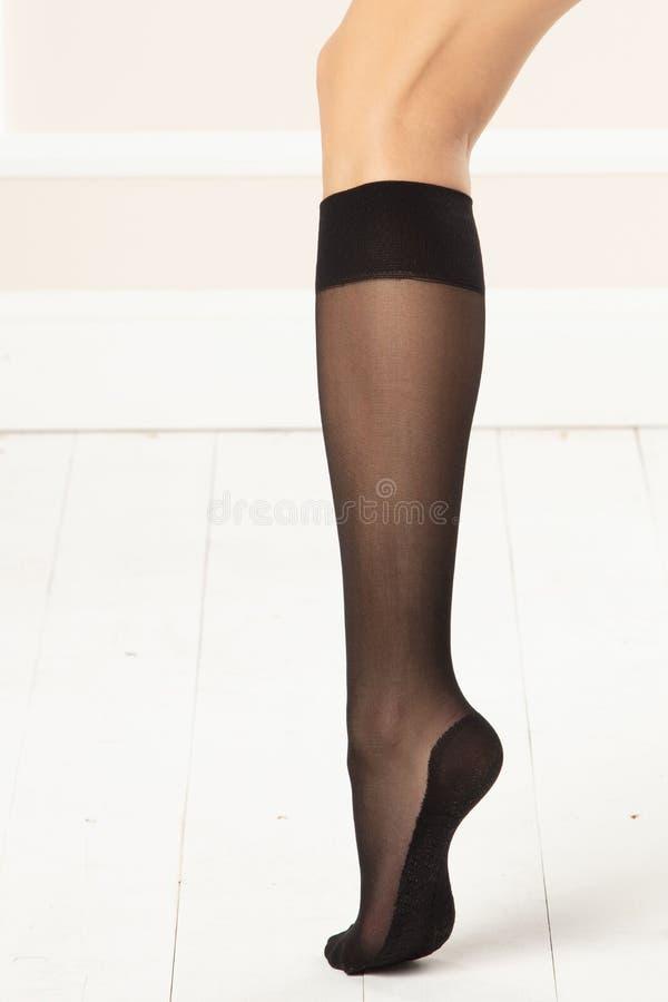 Pé feminino com joelho-elevações pretas imagens de stock royalty free