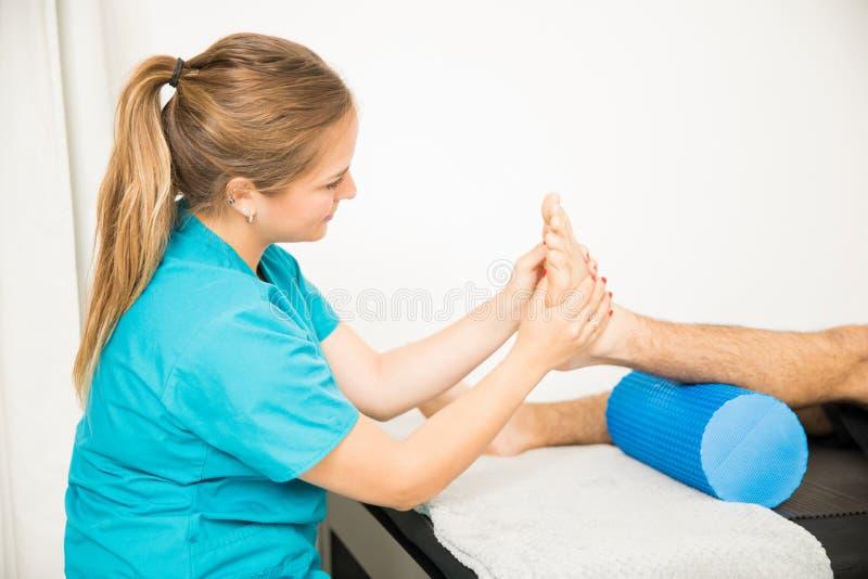 Pé paciente de massagem profissional do ` s da fisioterapia fotografia de stock royalty free