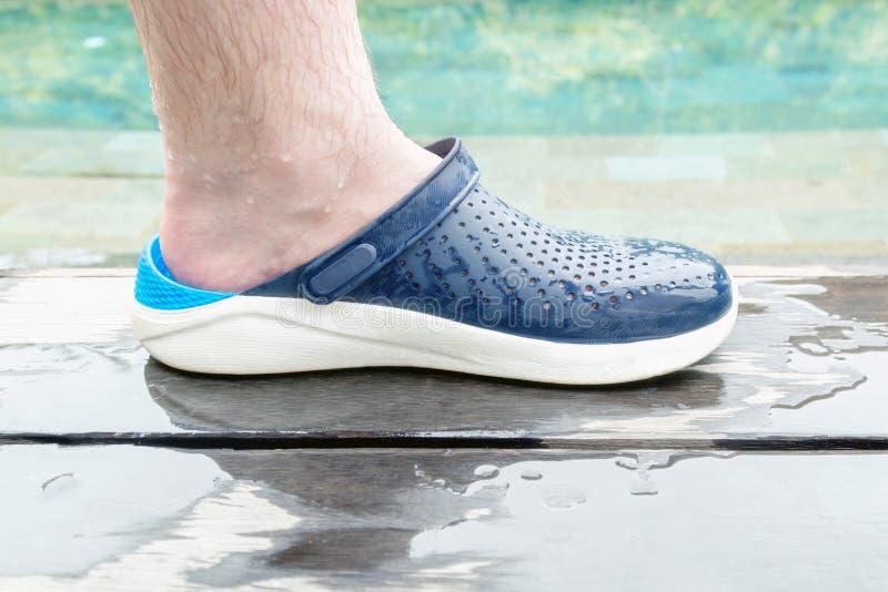 Pé peludo masculino molhado em sapatas de borracha confortáveis do verão pela piscina privada fotografia de stock royalty free