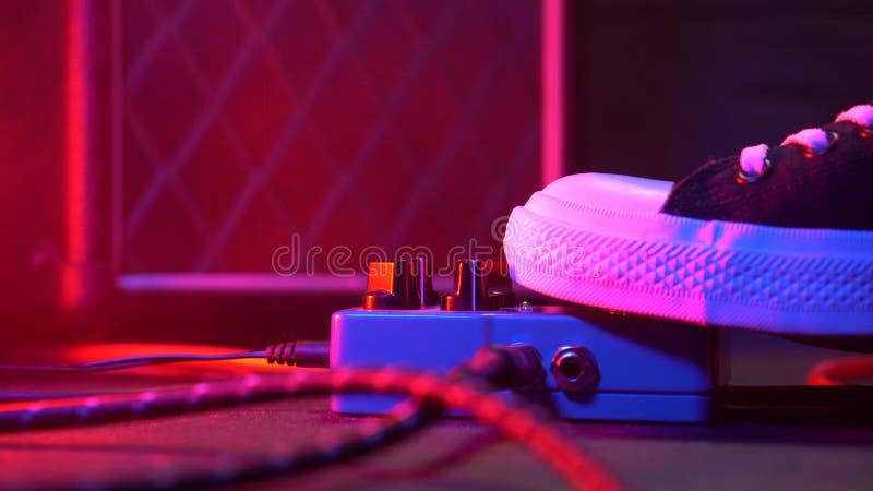Pédales et interrupteur à pied de guitare à l'intérieur de pièce d'enregistrement Fermez-vous des pédales de guitare et du pied d image stock