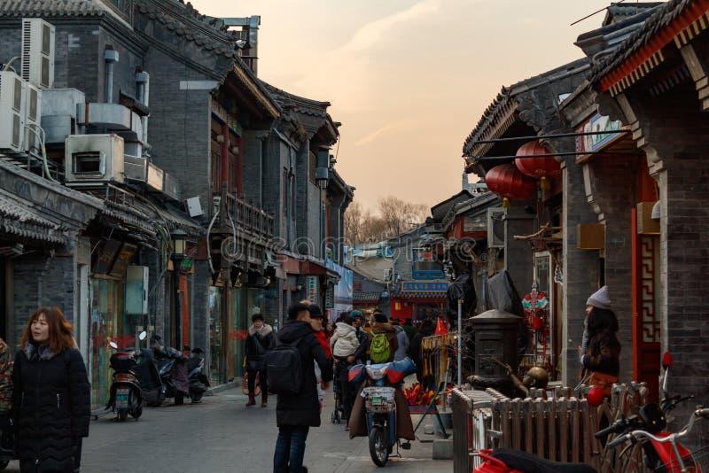 PÉKIN, CHINE - 24 DÉCEMBRE 2017 : Touristes et gens du pays marchant sur la rue traditionnelle de hutong de Pékin photo libre de droits