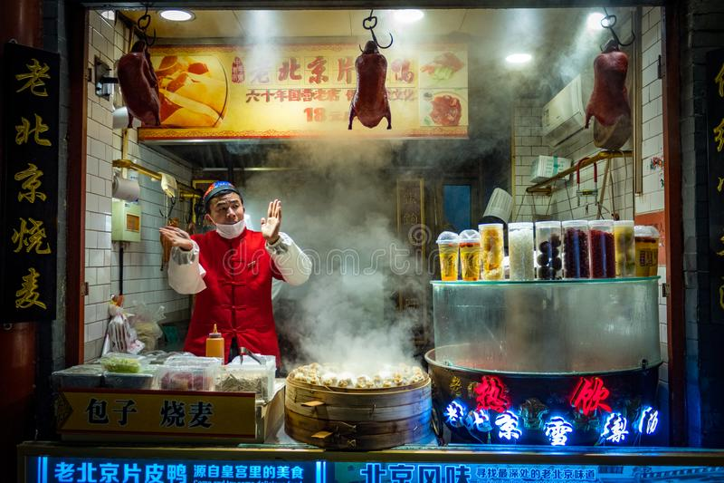 PÉKIN, CHINE - 20 DÉCEMBRE 2017 : Vendeur chinois du marché de nourriture de rue de Wangfujing vendant le canard de Pékin et le B image libre de droits