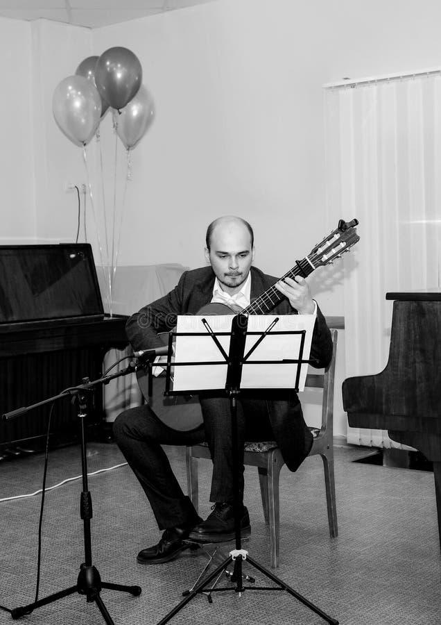 Pékin, photo noire et blanche de la Chine Le musicien regarde les notes et joue la guitare photographie stock