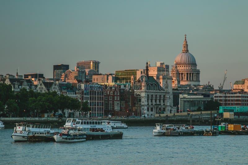 Péniches et bateaux de visite sur la Tamise au coucher du soleil photographie stock libre de droits