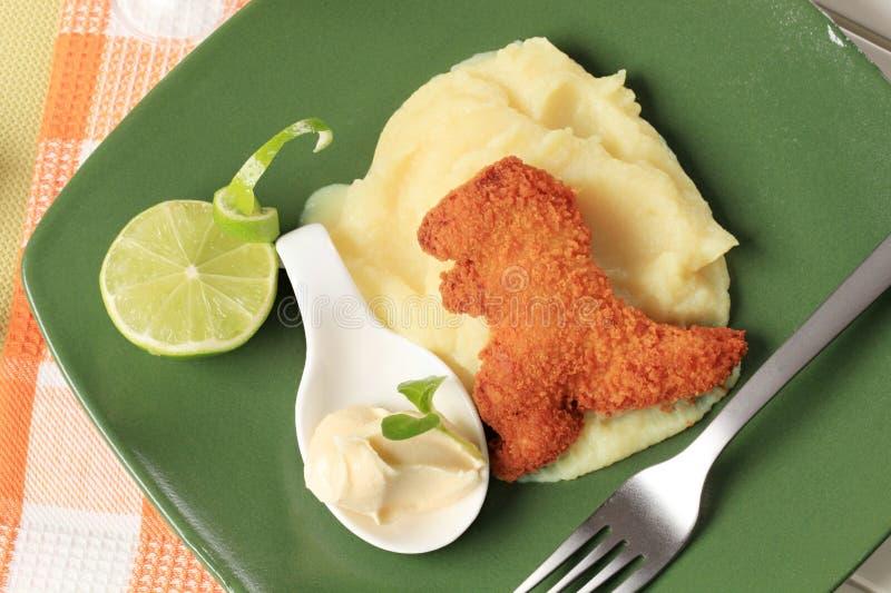 Pépite en forme de dinosaure frite avec de la purée de pommes de terre images stock