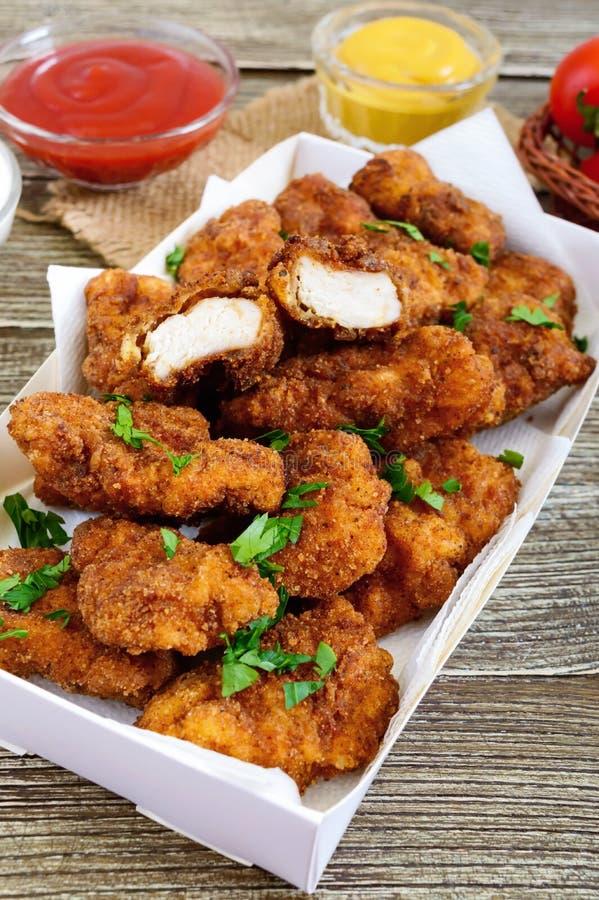 Pépites de poulet Morceaux de viande croustillante frite, avec différentes sauces image stock
