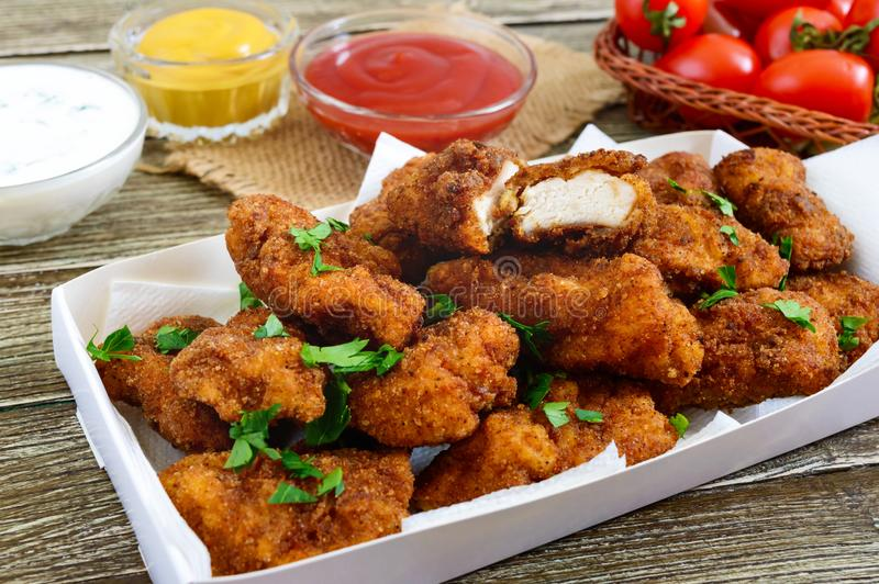 Pépites de poulet Morceaux de viande croustillante frite, avec différentes sauces sur une table en bois photos stock