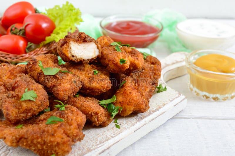 Pépites de poulet Morceaux de viande croustillante frite, sur le papier avec différentes sauces photographie stock