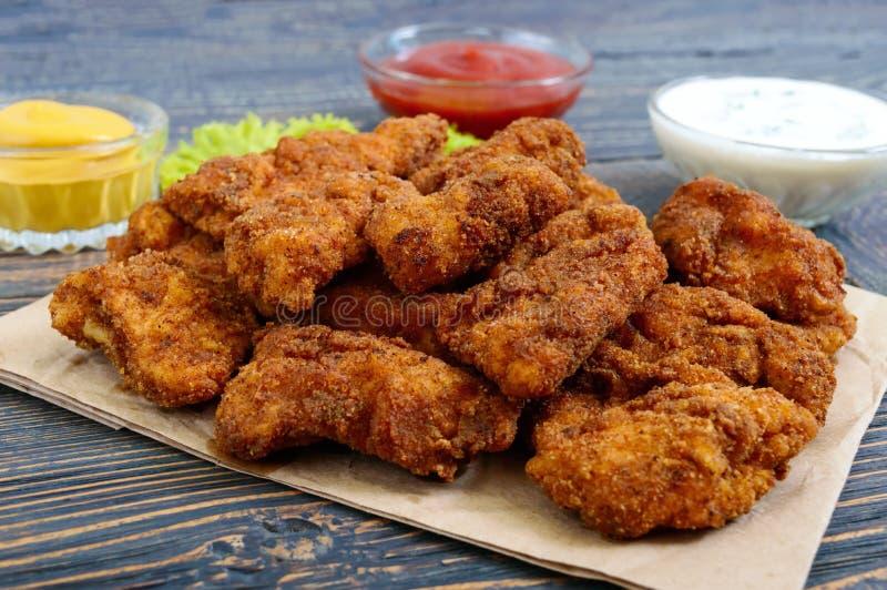 Pépites de poulet Morceaux de viande croustillante frite, sur le papier avec différentes sauces sur une table en bois photographie stock libre de droits