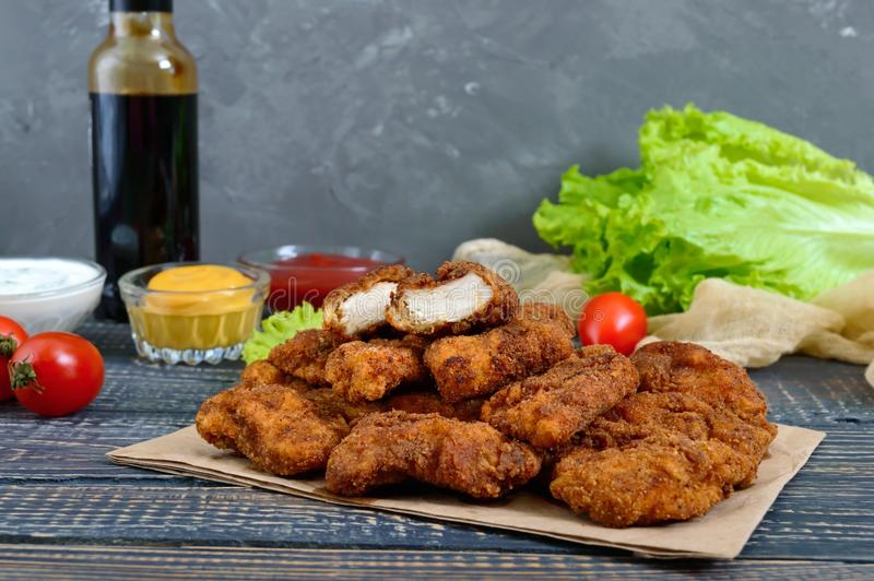 Pépites de poulet Morceaux de viande croustillante frite, sur le papier avec différentes sauces sur une table en bois image libre de droits