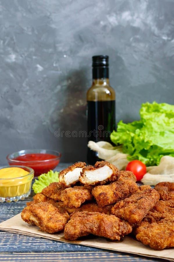 Pépites de poulet Morceaux de viande croustillante frite, sur le papier avec différentes sauces sur une table en bois photo stock