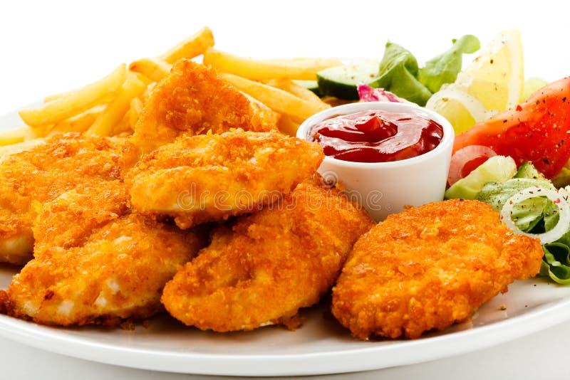 Pépites et légumes de poulet frit image stock