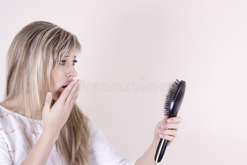 Pérdida de pelo Mujer joven deprimida que mira su cepillo para el pelo y que expresa negatividad foto de archivo libre de regalías