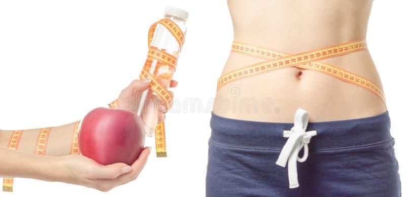 Pérdida de peso de la mujer joven que adelgaza con una botella del centímetro de la manzana de sistema disponible del modelo del  imágenes de archivo libres de regalías