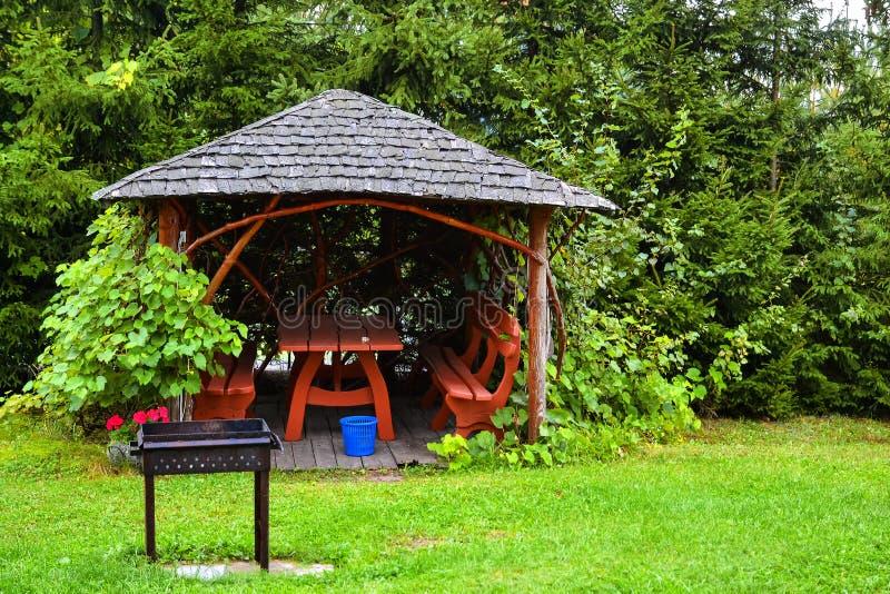 Pérgola de madera en el jardín del otoño Lugar de descanso con la tabla, b fotografía de archivo