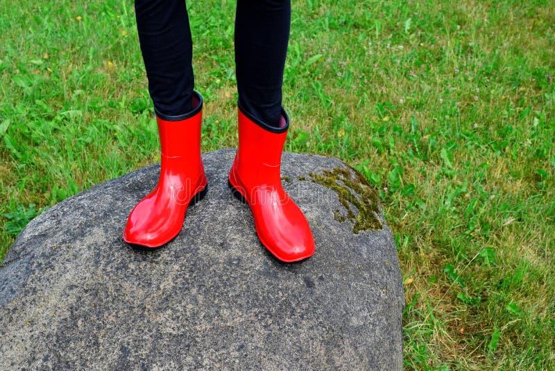 Pés adolescentes da menina que vestem botas de borracha vermelhas imagens de stock