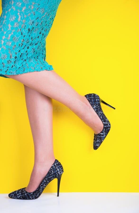 Pés bonitos da jovem mulher na saia colorida e em sapatas pretas com os saltos altos no fundo amarelo vibrante fotos de stock