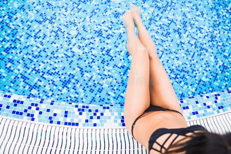 Pés bonitos da mulher que tomam sol perto da piscina Vocação do verão imagens de stock royalty free