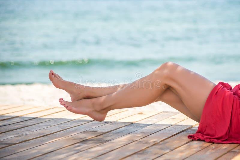 Pés bonitos do ` s da mulher na praia fotos de stock royalty free