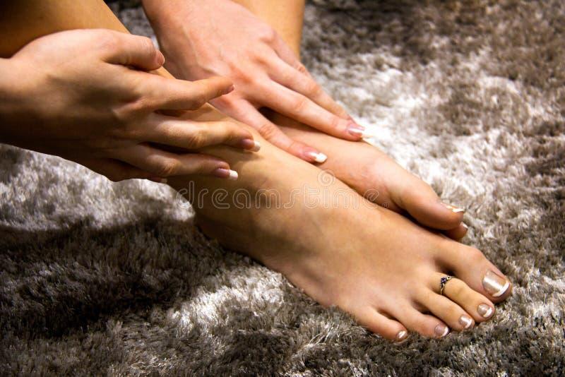Pés bonitos e mãos da mulher que tocam na pele macia, mimando o cuidado do pé e da mão, o tratamento de mãos francês luxuoso e o  imagens de stock royalty free