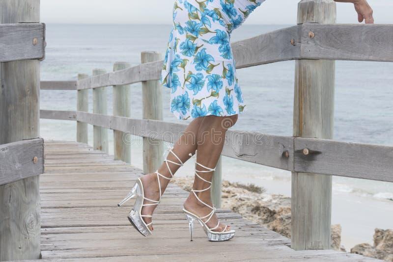 Pés bonitos nos saltos altos relaxado na praia fotografia de stock royalty free