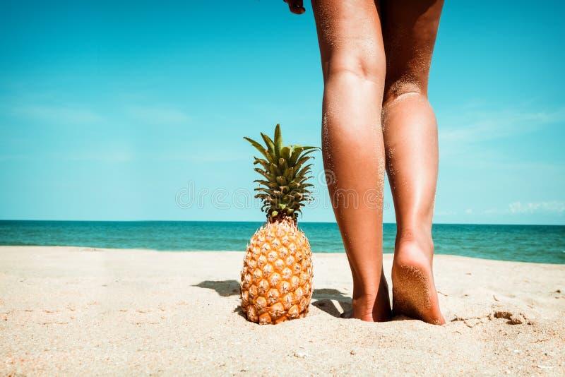 Pés bronzeados da jovem mulher que estão com o abacaxi na praia tropical no verão foto de stock royalty free