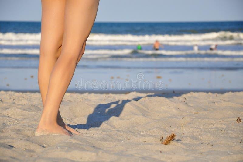 Pés caucasianos da mulher na praia com as ondas de oceano no fundo fotos de stock royalty free