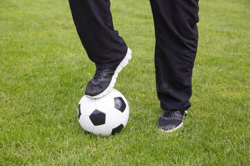 Pés com bola de futebol imagens de stock royalty free