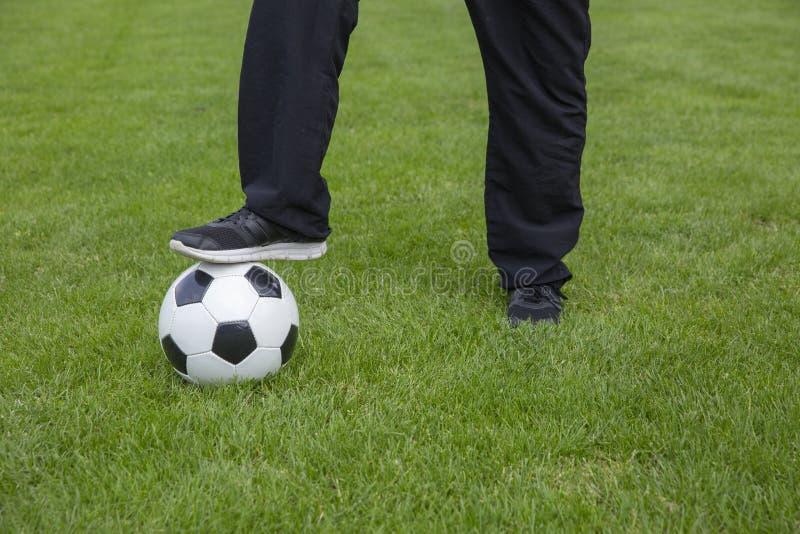 Pés com bola de futebol imagem de stock
