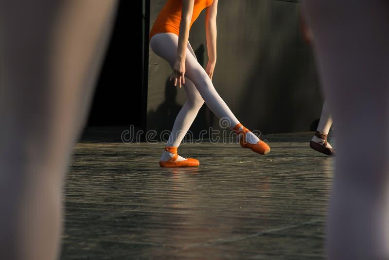 Pés da bailarina que dançam em sapatas de bailado na fase durante uma execução fotografia de stock