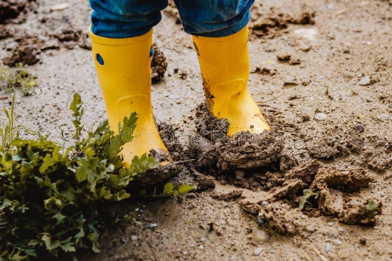 Pés da criança em botas de borracha enlameadas amarelas na lama molhada Bebê que joga com sujeira no tempo chuvoso imagens de stock