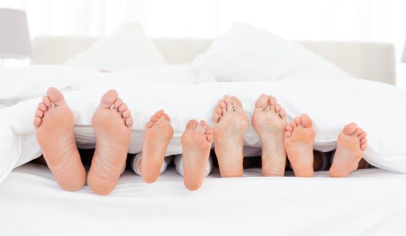 Pés da família na cama imagens de stock royalty free