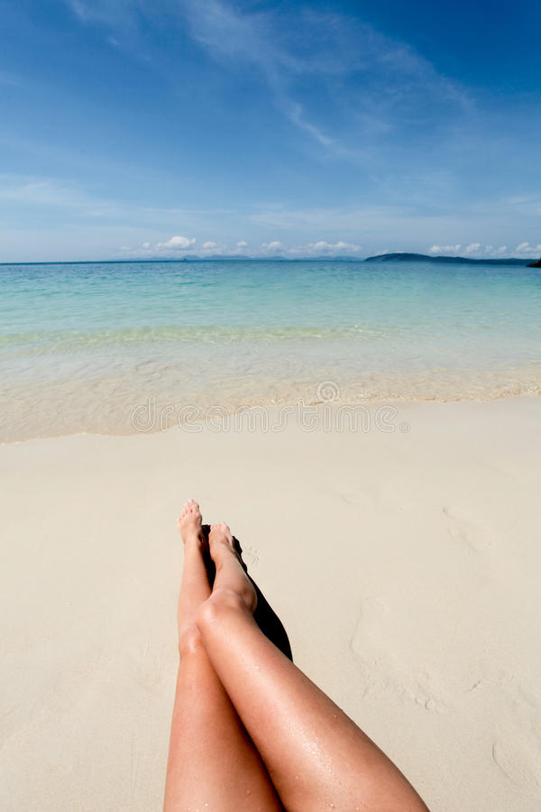 Pés da jovem mulher na praia fotos de stock royalty free