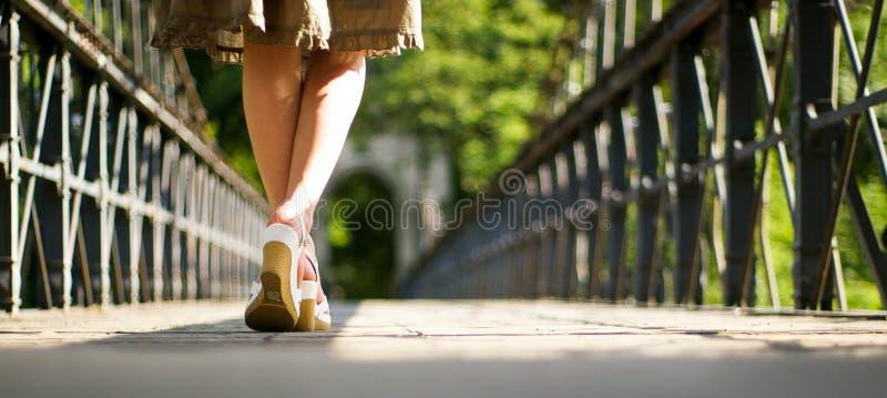 Pés da menina na saia na ponte imagem de stock royalty free
