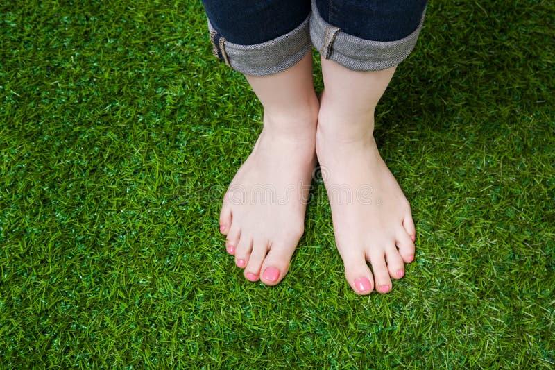 Pés da menina nas calças de brim que estão na grama verde foto de stock royalty free