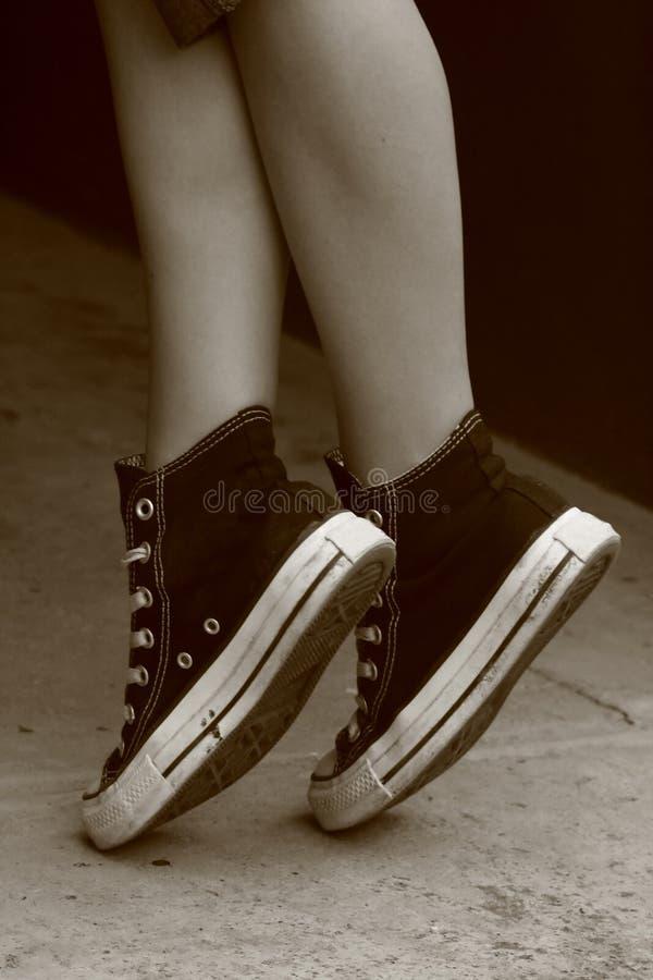 Pés da menina nas sapatilhas inversas (6) fotografia de stock