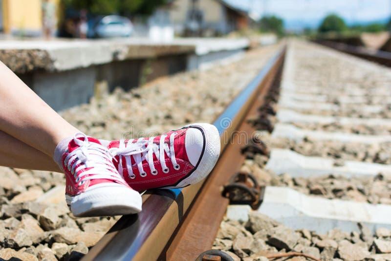 Pés da menina nas sapatilhas vermelhas que sentam-se pela estrada de ferro fotos de stock