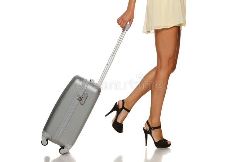 Pés da mulher com uma mala de viagem imagens de stock royalty free