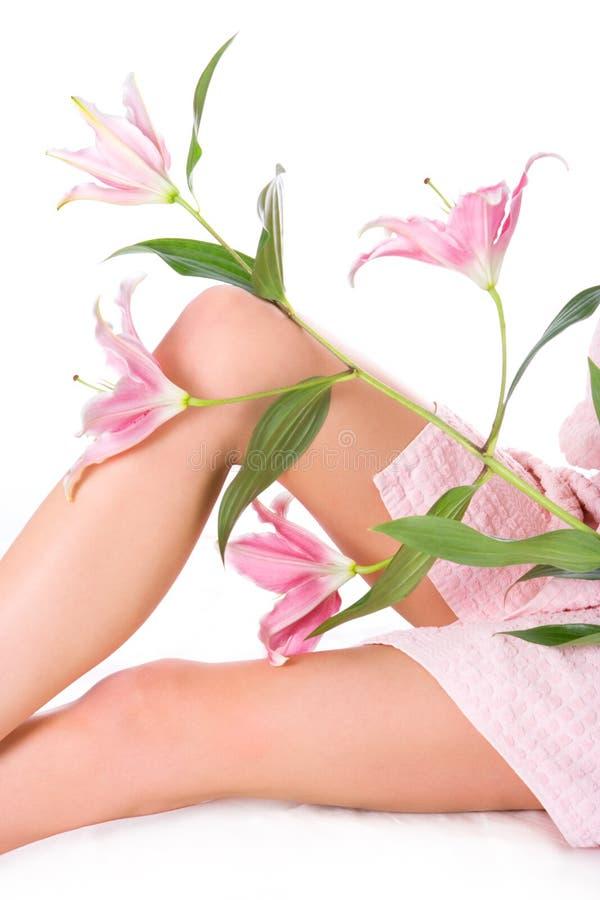 Pés da mulher da beleza com lírio cor-de-rosa imagem de stock royalty free