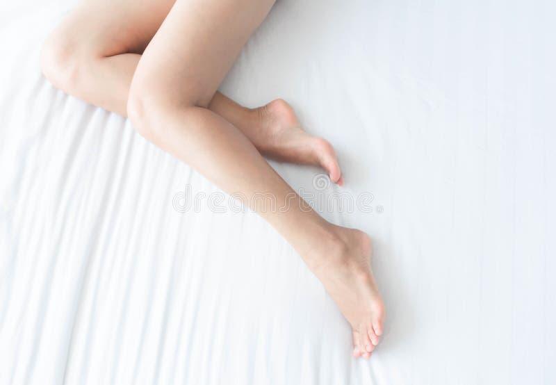 Pés da mulher do close up na cama branca com a janela clara excedente do formulário, a beleza e o conceito dos cuidados com a pel imagens de stock