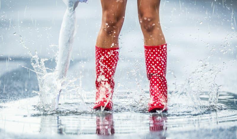 Pés da mulher em botas de borracha vermelhas pontilhadas com o guarda-chuva que salta nas poças da mola ou do outono do verão fotos de stock