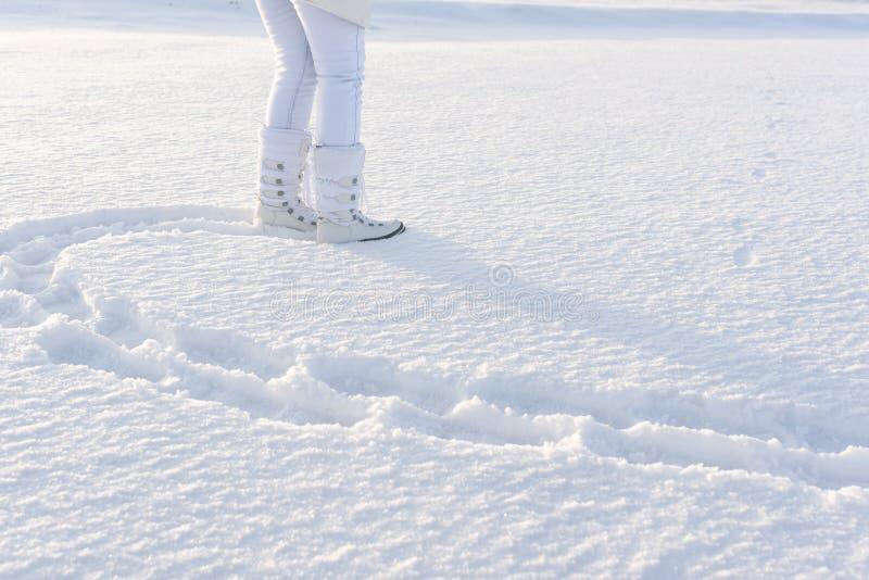 Pés da mulher em botas de neve Passos na neve profunda inverno branco B fotografia de stock