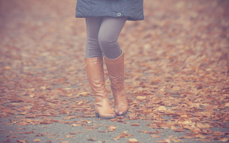 Pés da mulher em botas marrons Forma da queda fotografia de stock royalty free