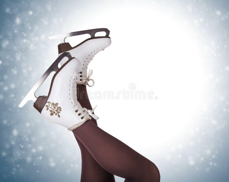 Pés da mulher em botas da patinagem no gelo imagens de stock royalty free
