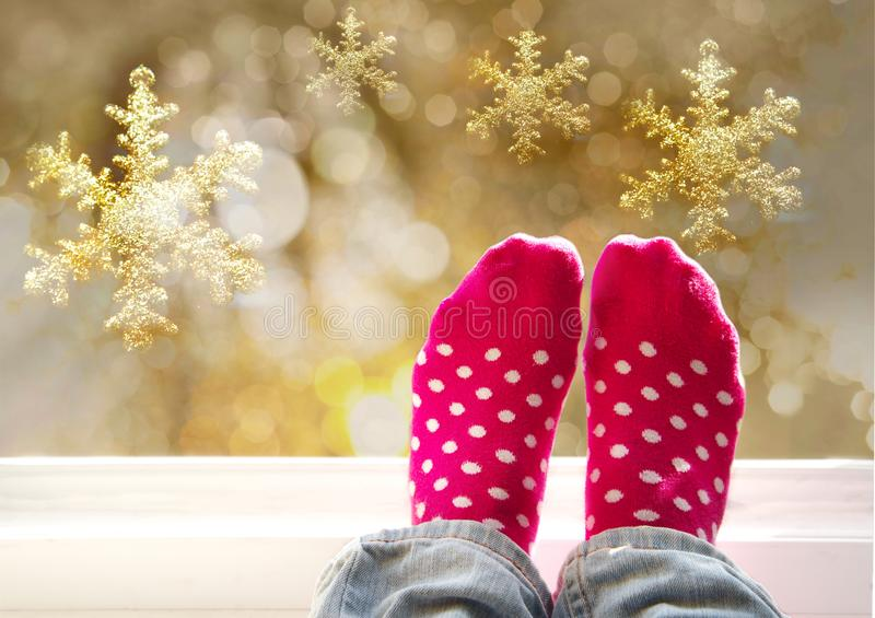 Pés da mulher em peúgas brancas cor-de-rosa bonitos do ponto na janela com floco de neve dourado e feriado claro de incandescênci fotografia de stock