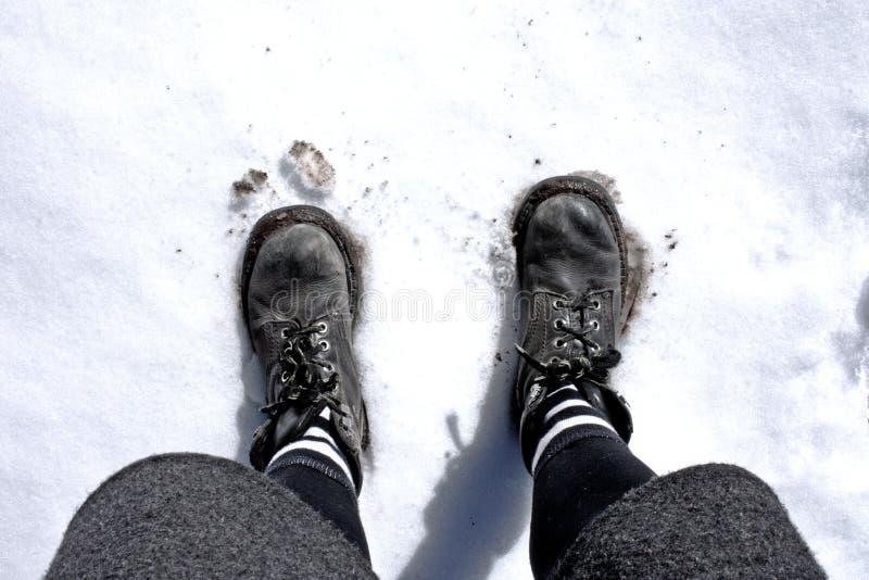 Pés da mulher na neve com luz solar do ângulo alto imagens de stock royalty free