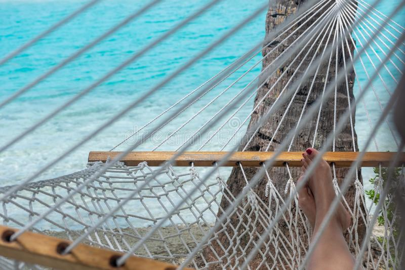 P?s da mulher na rede na praia, fundo azul do mar, Aitutaki fotografia de stock